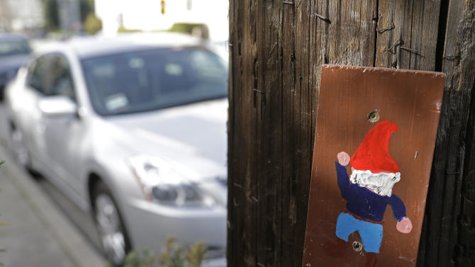A hand painted portrait of a gnome is shown on a utility pole near Lake Merritt Tuesday, Jan. 29, 2013 in Oakland, Calif. Small paintings of gnomes that have popped up on utility poles have become a community sensation in Oakland, prompting Pacific Gas & Electric Co. to say Tuesday that it will keep them in place for now. The portraits on 6-inch blocks of wood began going up last year in an apparent effort to brighten up the blue-collar California city. There are currently more than 2,000 of the images on utility poles, with many screwed to the bases. (AP Photo/Eric Risberg)