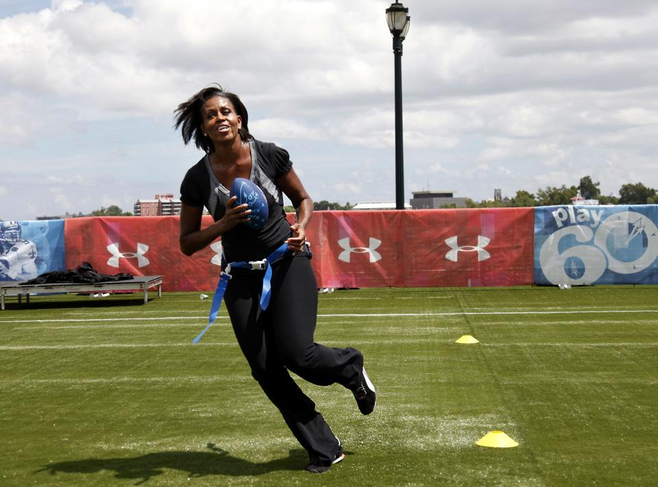 FILE - In this Sept. 8, 2010, file photo, first lady Michelle Obama turns and runs after catching a pass while participating in the Let's Move!  Campaign and the NFL's Play 60 Campaign festivities with area youth in New Orleans. (AP Photo/Gerald Herbert, File)