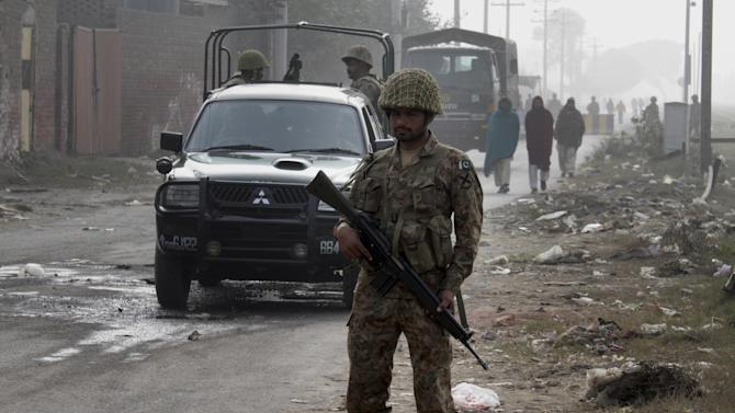 Pakistan army troops patrol on a road leading to the central prison on the outskirts of Lahore, Pakistan, Saturday, Dec. 20, 2014. Pakistani authorities beefed up security around prisons ahead of executions. Pakistani officials said on Friday authorities have hanged two convicted militants in the first executions following the reinstatement of the death penalty in the wake of this week's Peshawar school massacre. (AP Photo/K.M. Chaudary)