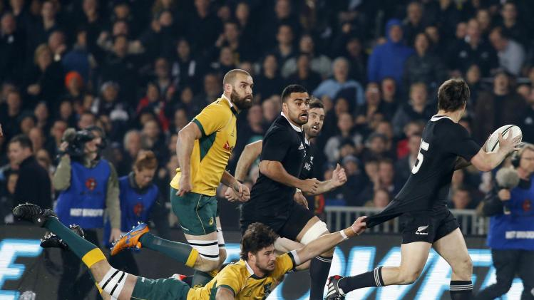 Smith of New Zealand's All Blacks is tackled by Adam Ashley-Cooper of Australia's Wallabies during their Bledisloe Cup rugby championship match in Auckland