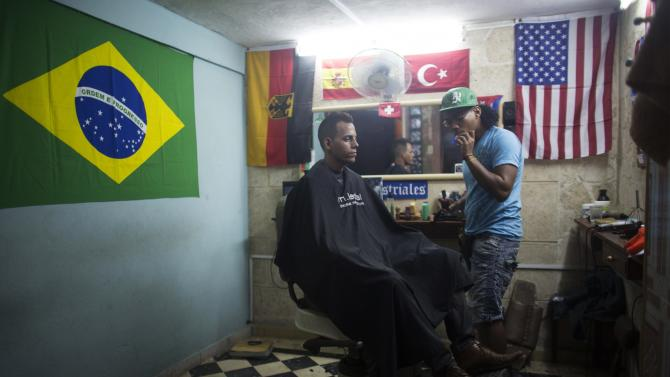 Miguel Angel Moreira, 26, cuts the hair of street vendor Dainer Guerra, 29, at his barber shop in downtown Havana