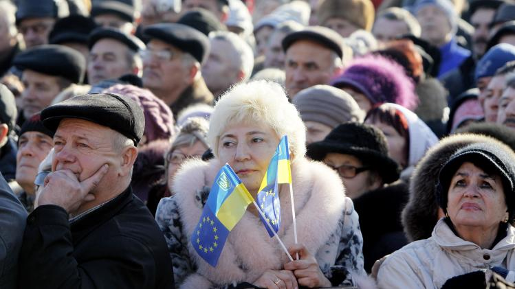 A pro-European integration protester holds Ukranian flags during a rally in Independence square in Kiev