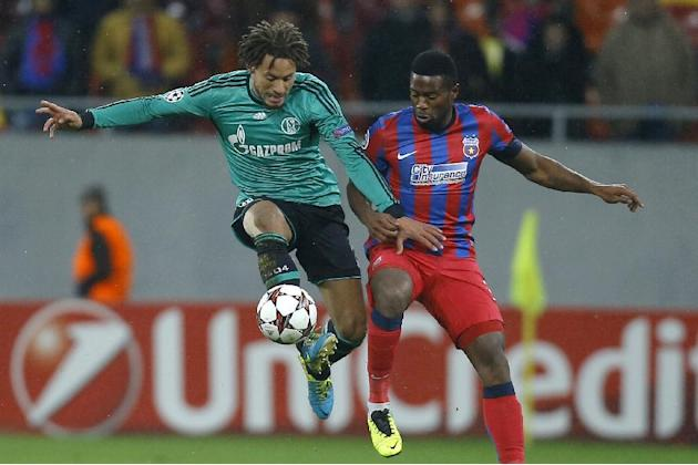 Schalke's Jermaine Jones, left, in action with Bucharest's Fernando Varela, during their Champions League Group E soccer match, at the National Arena in Bucharest, Romania, Tuesday, Nov. 26, 2013