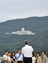 Unification Church followers take pictures in front of a large hillside museum, where the body of the late Unification Church leader Sun Myung Moon is placed, in the church's estate in Gapyeong, about 60 km east of Seoul, on September 14, a day before his funeral