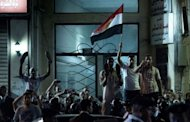 Egyptian protesters gather on a street near the US Consulate as US Secretary of State Hillary Clinton attends a flag-raising ceremony at the Consulate General in the mediterranean city of Alexandria. Clinton met Sunday with Egypt's top military leaders, urging them to support a transition to civilian rule as a political struggle triggers fears that rights could be eroded