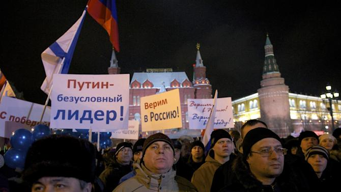 """People rally in support of Russian Prime Minister and presidential candidate Vladimir Putin following an election day, outside the Kremlin in Moscow, Sunday, March 4, 2012. Vladimir Putin has claimed victory in Russia's presidential election, which the opposition and independent observers say has been marred by widespread violations. Putin made the claim at a rally of tens of thousands of his supporters just outside the Kremlin, thanking his supporters for helping foil foreign plots aimed to weaken the country. Posters read """"Putin is indisputable leader,"""" """"We believe in Russia."""" (AP Photo/Harry Engels)"""