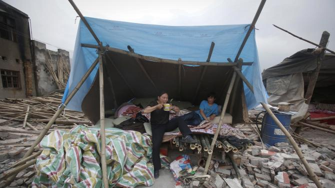 A woman eats instant noodles at a shelter near her damaged home in Longmen Township in Lushan County in southwest China's Sichuan province Sunday, April 21, 2013. Saturday's earthquake in Sichuan province killed more than 200 people, China's Xinhua News Agency said. (AP Photo)
