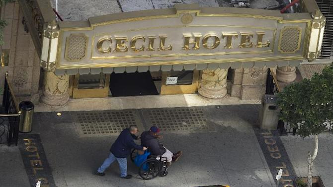 Two men pass by the  front of the Cecil Hotel in Los Angeles Thursday, Feb. 21, 2013.  Canadian tourist Elisa Lam  had been missing for about two weeks when officials at the Cecil Hotel found her body in a water cistern on the hotel roof. Guest complaints about low water pressure prompted a maintenance worker to make the gruesome discovery Tuesday, and officials were trying to determine if the 21-year-old was killed or if her death was a bizarre accident. (AP Photo/Damian Dovarganes)