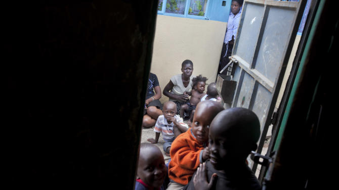 In this photo taken Tuesday, Dec. 6, 2011, neighboring children sit in the courtyard outside the house of Mary and Ishmael Abongo, both of whom are HIV positive, in the Mathare slum of Nairobi, Kenya. The U.N.'s Food and Agriculture Organization says that 2011 prices for staple foods are almost twice as high as they were in 2009, with rising prices and a lack of new funds for HIV programs meaning countless poor families must decide whether to focus on the health of an HIV-positive adult or on a child's hunger. (AP Photo/Ben Curtis)