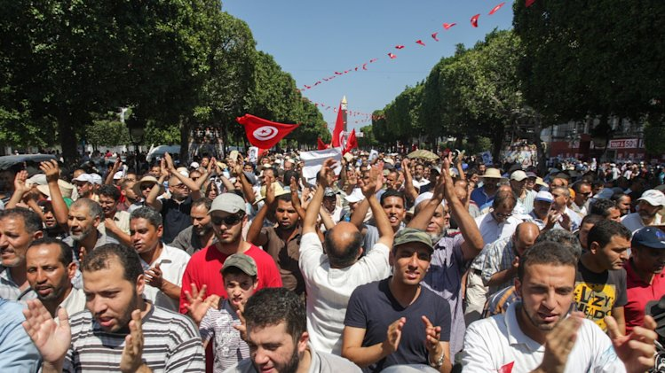 CAPTION CORRECTS THE SPELLING OF MOHAMMED Supporters of the Islamist Ennahda movement march in the streets of Tunis during a demonstration to condemn the assassination of politician Mohammed Brahmi in Tunisia, Friday, July 26, 2013. Mohammed Brahmi was shot 14 times in front of his home within sight of his family on Thursday, plunging the country into a political crisis and unleashing demonstrations around the country blaming the government for the assassination. (AP Photo/Amine Landoulsi)