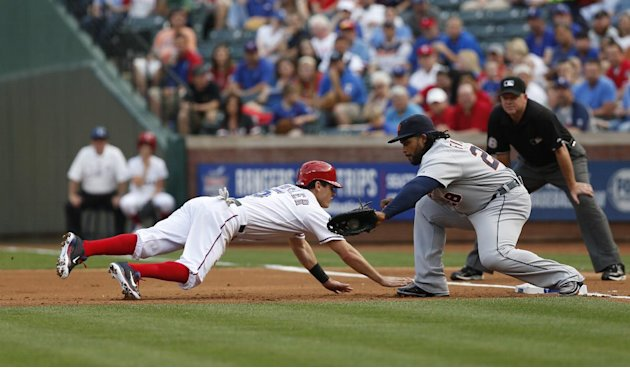 Texas Rangers' Ian Kinsler dives back to first base ahead of the tag by Detroit Tigers first baseman Prince Fielder (28) in the first inning of a baseball game, Thursday, May 16, 2013, in Arlington, T