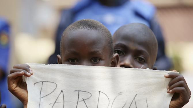 A child holds a sign before Pope Francis' visit in the refugee camp of Saint Sauveur in the capital Bangu
