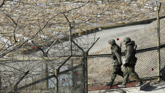 """South Korean army soldiers patrol along a barbed-wire fence at the Imjingak Pavilion in Paju, South Korea, near the demilitarized zone (DMZ) of Panmunjom, Sunday, Jan. 27, 2013. North Korean leader Kim Jong Un convened top security and foreign affairs officials and ordered them to take """"substantial and high-profile important state measures,"""" state media said Sunday, indicating that he plans to push forward with a threat to explode a nuclear device in defiance of the United Nations. (AP Photo/Ahn Young-joon)"""