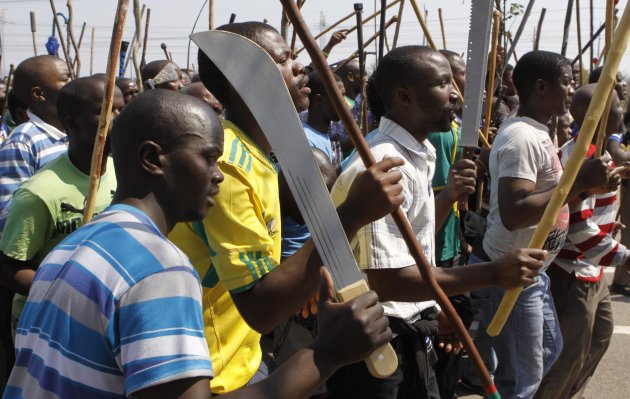 Striking mine workers armed with machetes, sticks and spears march to a smelter plant at the Lonmin Platinum Mine near Rustenburg, Wednesday, Sept, 12, 2012 to deliver a memorandum to mine management and to ensure that workers had not reported for duty. Miners are refusing to return to work until their demands over low pay and working conditions are met. Strikes are spreading to nearby gold mines. (AP Photo/Denis Farrell)