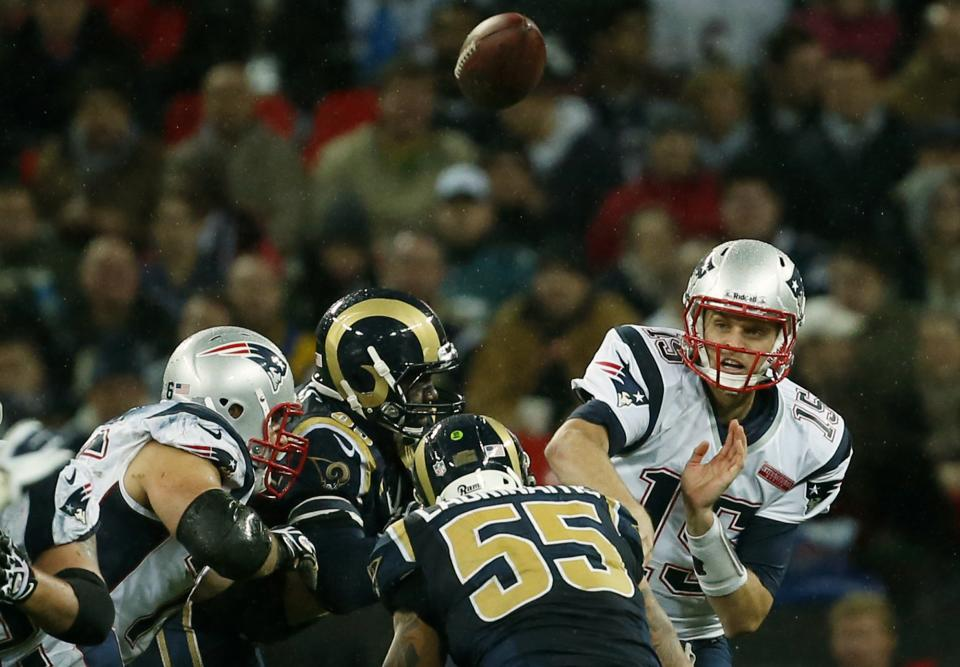 New England Patriots quarterback Ryan Mallett, makes a throw with St. Louis Rams middle linebacker James Laurinaitis, 55, centre, during the second half of a NFL football game at Wembley Stadium, London, Sunday, Oct. 28, 2012. (AP Photo/Matt Dunham)