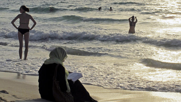 FILE - In this Thursday, Sept. 6, 2012 file photo, a woman reads the Quran on a beach as people in bikinis sunbathe and swim at sunset in Dubai, United Arab Emirates. Bikinis and briefs are no longer welcome on some sands in the United Arab Emirates. Authorities in Ras al-Khaimah, the northernmost emirate in the UAE, have posted signs on public beaches warning of possible fines for revealing swim wear such as two-piece bikinis for women and brief trunks for men. (AP Photo/Hassan Ammar)