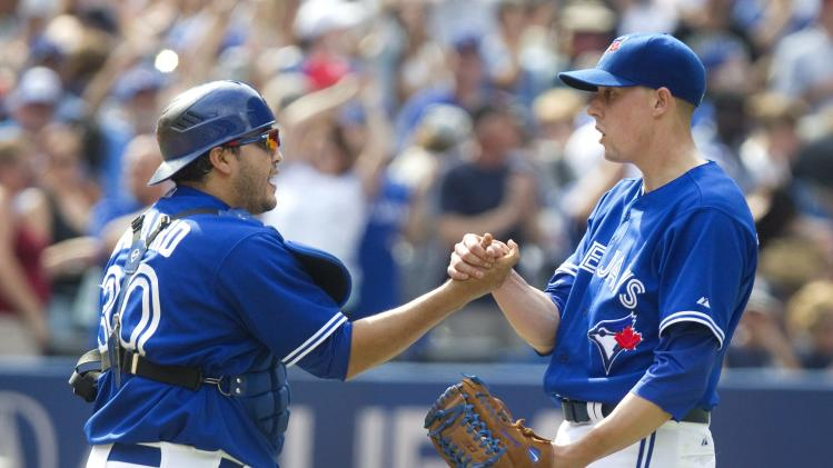 Toronto Blue Jays pitcher Aaron Sanchez, right, gets a hand shake from catcher Dioner Navarro after they defeated the New York Yankees 2-0 in a baseball game in Toronto on Saturday, Aug. 30, 2014. (AP Photo/The Canadian Press, Fred Thornhill)