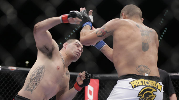 Cain Velasquez, left, throws a punch against Antonio Silva in the first round of the UFC 160 mixed martial arts heavyweight title bout, Saturday, May 25, 2013, in Las Vegas. Velasquez won by technical knockout. (AP Photo/Julie Jacobson)