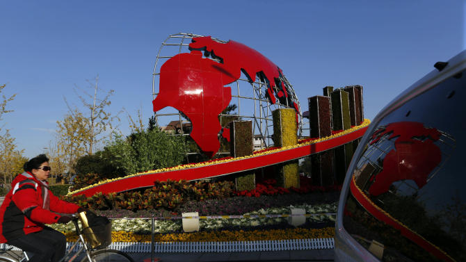 In this photo taken Monday, Nov. 12, 2012, a woman cycles by a floral decoration set up for the 18th Communist Party Congress held in Beijing, China. The Chinese capital's administrators have bedecked the city with towers of flower installations and other eye-catching landscaping decorations. State media say 20 million pots of flowers are being used in more than a hundred locations in preparation for the once-a-decade party congress to usher in a new generation of leaders.  (AP Photo/Vincent Yu)