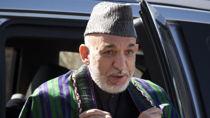 Afghan President Hamid Karzai leaves the car as he arrives to address the Afghan Parliament in Kabul, Afghanistan, Wednesday, March 6, 2013. Karzai called on his security forces to end incidents of torture and abuse of the Afghan people and said that Afghan forces are violating their own people's rights, making it harder for him to raise the issue when abuses are carried out by foreigners.  (AP Photo/Anja Niedringhaus)
