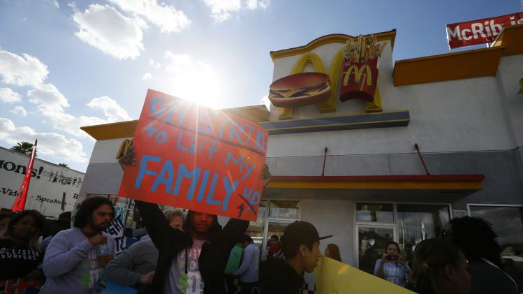 Cory Norman, 23, holds a sign during a protest outside McDonald's in Los Angeles