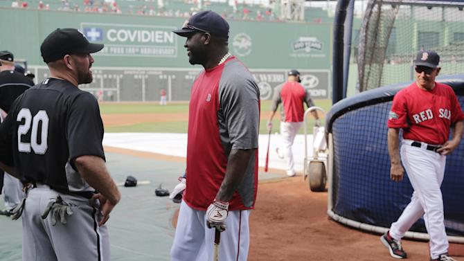 Chicago White Sox third baseman Kevin Youkilis, left, talks with his former teammate, Boston Red Sox designated hitter David Ortiz, during batting practice before a baseball game at Fenway Park in Boston, Monday, July 16, 2012. Youkilis returned to Fenway, where he was a member of the 2004 and 2007 World Series Champion teams, for the first time since being traded. At rear right walking away is Red Sox manager Bobby Valentine, his former manager. (AP Photo/Charles Krupa)