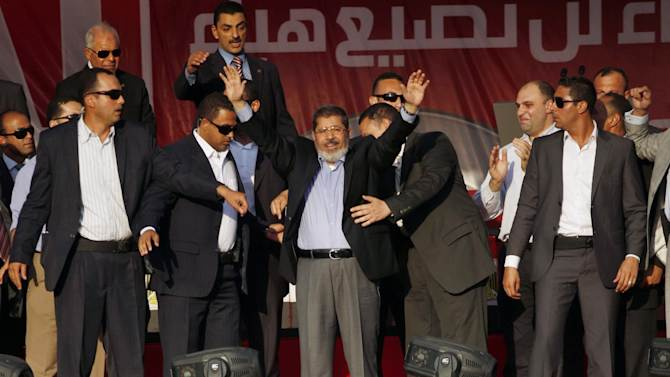 Egypt's President-elect Mohammed Morsi waves to supporters before giving a speech at Tahrir Square in Cairo, Egypt, Friday, June 29, 2012. In front of tens of thousands of cheering supporters, Egypt's first Islamist and civilian president-elect vowed that nobody can take away his authority and symbolically read an oath of office on the eve of his official inauguration.  (AP Photo/Khalil Hamra)