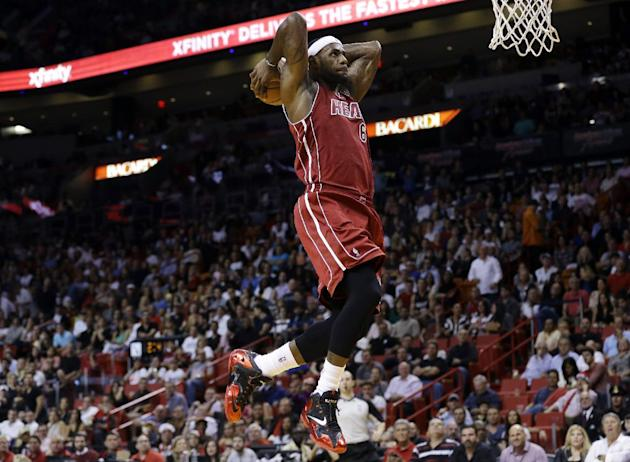 Miami Heat's LeBron James goes up to dunk in the first half of an NBA basketball game against the Sacramento Kings, Friday, Dec. 20, 2013, in Miami
