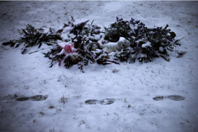 Footprints are seen in the snow next to the grave of six-year-old Charlotte Helen Bacon on Christmas morning at the Newtown Village Cemetery Newtown, Connecticut