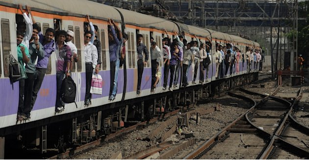 Passengers travel on a crowded train in Mumbai on March 14, 2012. Indian Railways Minister Dinesh Trivedi presents the railway budget for the fiscal year to March 2012-13 in Parliament on March 14. Pi