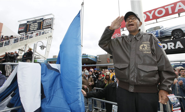 Veteran George Hickman, a Tuskegee Airman during World War II and from Seattle, salutes before he raises the 12th Man Flag before the beginning of the NFL football game against the Ravens as part of t
