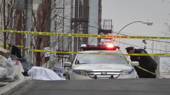 Police guard a sheet-covered plastic bag, left, at a hilltop intersection on Eagle Avenue in the Bronx borough of New York, Tuesday, Feb. 26, 2013. A man out walking his dog early Tuesday morning discovered the dismembered remains of a woman in heavy duty plastic garbage bags, police said. The body is believed to be that of a 45-year-old woman. Her name was not immediately released, and the medical examiner's office was working to determine a cause of death.  (AP Photo/Bebeto Matthews)