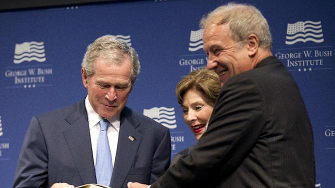 Former President George W. Bush with former first lady Laura Bush, center, is presented with a collection of writings by former Czech President Vaclav Havel by Martin Palous, head of the Vaclav Havel Library Foundation during a gathering to celebrate the successes of dissidents and activists in their fight to be free, Tuesday, May 15, 2012, at the George W. Bush Presidential Center in Washington.  (AP Photo/Manuel Balce Ceneta)