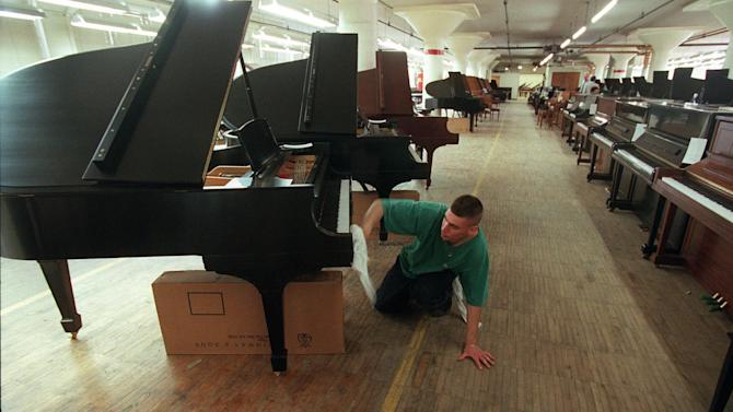 FILE - In a May 17, 1996 file photo, John Volastro, who works in the restoration department of Steinway and Sons, applies the finishing touches to a Steinway piano at piano maker's factory in the Queens Borough of New York. The famed piano maker Steinway is being acquired by private equity firm Kohlberg & Co. for about $438 million. Steinway, which has been in business for 160 years, said previously that was looking into selling the company. The board of the Waltham, Mass., company unanimously recommended Monday, July 1, 2013 that shareholders tender their stock. (AP Photo/Adam Nadel, File)