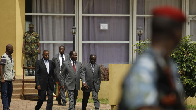 Alassane Ouattara, in red tie, is watched over by armed guards as he walks with advisors and staff in the garden of the Golf Hotel in Abidjan, Ivory Coast, Thursday, Jan. 6, 2011. Ouattara, the man recognized as the winner of Ivory Coast's recent presidential election, called Thursday for special forces from West African nations to remove Ivory Coast's incumbent president Laurent Gbagbo in a commando operation.(AP Photo/Rebecca Blackwell)