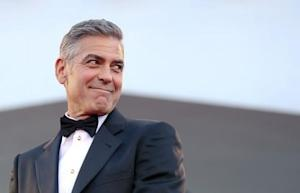 """U.S. actor Clooney smiles as he arrives on the red carpet for the premiere of """"Gravity"""" at the 70th Venice Film Festival in Venice"""