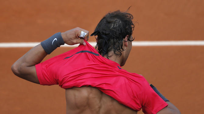 Rafael Nadal of Spain changes shirts in his third round match against Eduardo Schwank of Argentina at the French Open tennis tournament in Roland Garros stadium in Paris, Saturday June 2, 2012. (AP Photo/Christophe Ena)