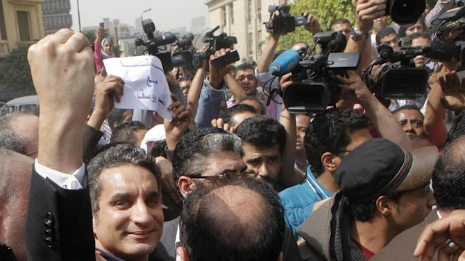 Egyptian popular television satirist Bassem Youssef, who has come to be known as Egypt's Jon Stewart, waves to is supporters as he enters Egypt's state prosecutors office in Cairo, Egypt, Sunday, March 31, 2013 for accusations of allegedly insulting Islam and the country's leader. The acceleration in legal action targeting protesters, activists and critics comes against a backdrop of continued unrest in the country. (AP Photo/Amr Nabil)