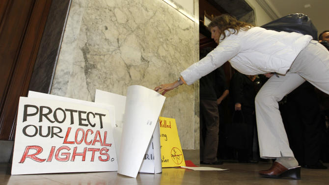 A woman picks up a sign as she leaves the the Pennsylvania state Supreme Courtroom in Pittsburgh where the court was hearing arguments from seven municipalities challenging portions of a new law that regulates natural gas exploration on  Wednesday, Oct. 17, 2012. (AP Photo/Keith Srakocic)
