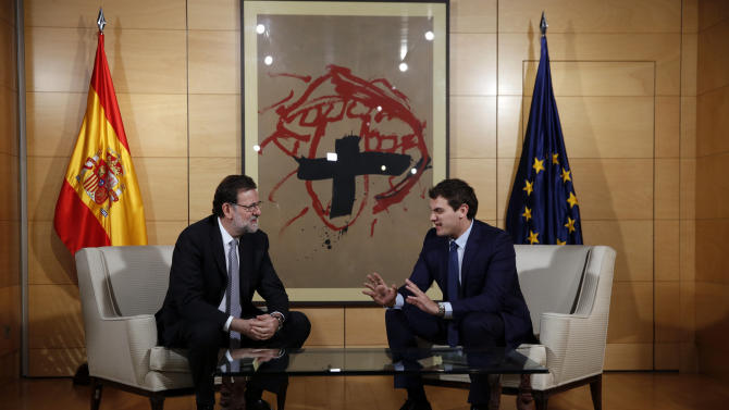 Spanish acting PM Rajoy and Ciudadanos party leader Rivera speak as they pose for the media before the start of their meeting at the Spanish Parliament in Madrid