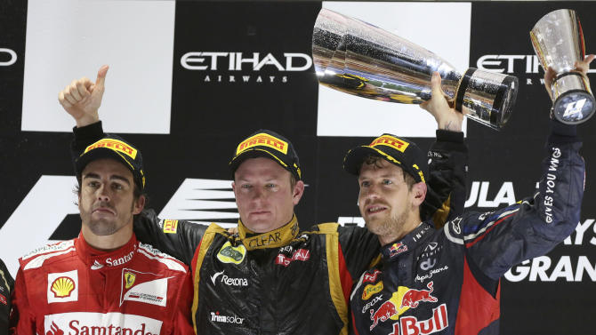 Lotus driver Kimi Raikkonen of Finland, winner, center, Ferrari driver Fernando Alonso of Spain, left, second place and Red Bull driver Sebastian Vettel of Germany, right, third place pose on the podium after the Emirates Formula One Grand Prix, at the Yas Marina racetrack, in Abu Dhabi, United Arab Emirates, Sunday, Nov. 4, 2012. (AP Photo/Luca Bruno)