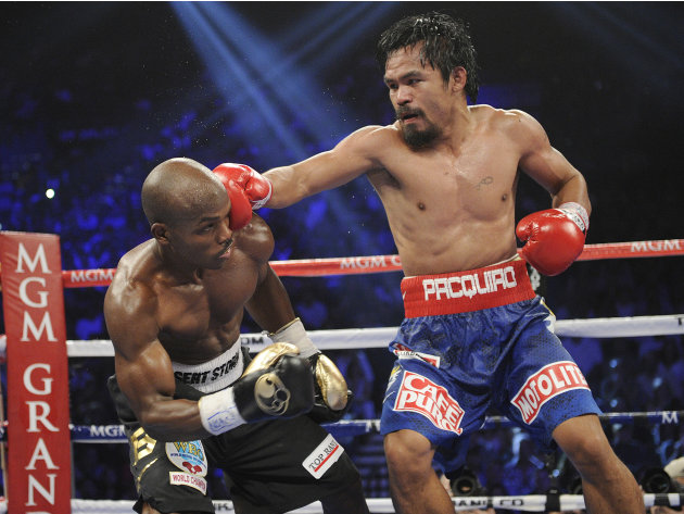 Manny Pacquiao, right, from the Philippines, connects with a right to the head of Timothy Bradley, from Palm Springs, Calif., in their WBO world welterweight title fight Saturday, June 9, 2012, in Las