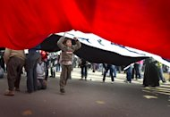"A young boy is seen under a giant flag carried by anti military rule protestors at Tahrir square in Cairo on December 2. Egypt's biggest political group the Muslim Brotherhood clashed with the country's army leaders, accusing them of trying to ""marginalise"" parliament over the writing of a new constitution. (AFP Photo/Odd Andersen)"