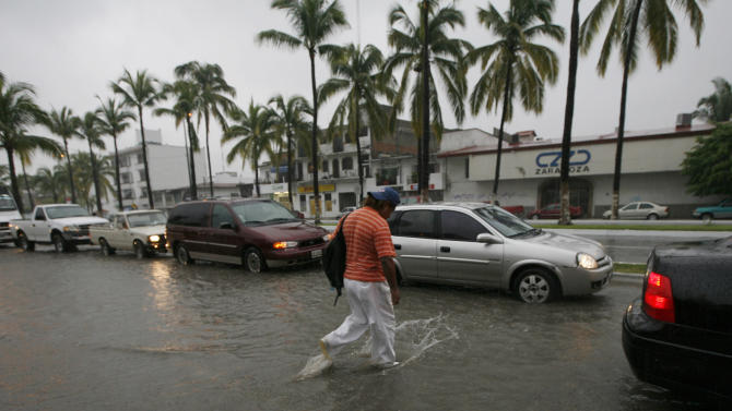 A pedestrian walks on a flooded street in Puerto Vallarta, Mexico, Monday Oct. 10, 2011. Hurricane Jova strengthened to a major, Category 3 hurricane Monday as it marched toward Mexico's Pacific coast. (AP Photo/Marco Ugarte)