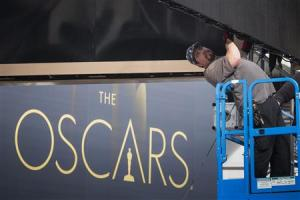 A man arranges a digital display above the red carpet during preparations for the 86th Academy Awards in Hollywood, California