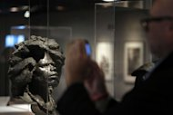 A visitor looks at an head displayed during the exhibition entitled &quot;Cheveux Cheris&quot; at the Quai Branly Museum in Paris