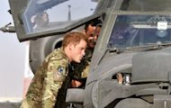 Britain's Prince Harry examines the interior of an Apache helicopter with a member of his squadron in Helmand Province, Afghanistan, on September 7. The base where he is stationed has come under attack and two US Marines were killed