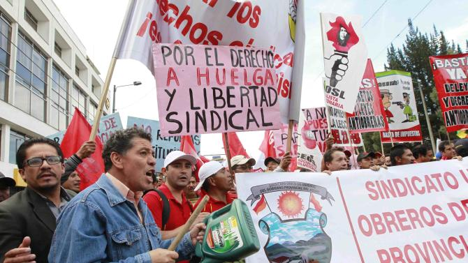 Demonstrators shout slogans while holding signs during a rally against the government in Quito