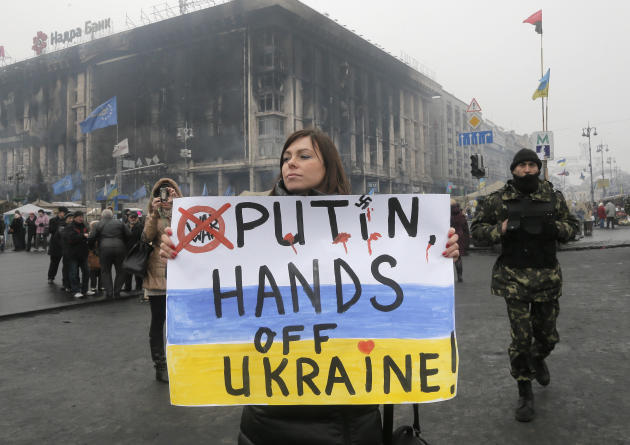 A woman holds a poster against war at Kiev's Independence Square, in Ukraine, Thursday, March 6, 2014. The Heads of State of the EU will meet Thursday in emergency session in Brussels to discuss t