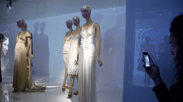 "A woman photographs a display of fashions by Elsa Schiaparelli and Miuccia Prada at the Metropolitan Museum of Art, Monday, May 7, 2012 in New York. The  show ""Schiaparelli and Prada, Impossible Conversations,"" opens May 10 and continues through Aug. 19. (AP Photo/Mark Lennihan)"